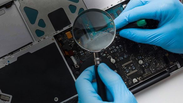 Mann reparerer laptop med forstørrelsesglass